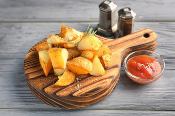 Wooden board with delicious baked potato wedges and sauce on table