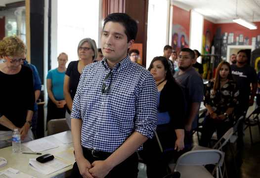 DACA recipient Ernesto Delgado stands for a prayer during a renewal application process at the immigration ministry at Lincoln Methodist Church in Chicago