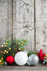Red, silver and white christmas ornaments, xmas tree on rustic wood background with sparkle bokeh lights. Merry christmas greeting card. Winter holiday theme. Happy New Year. Space for text.