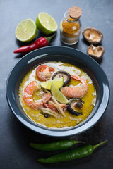 Thai spicy green curry soup with cooking ingredients, selective focus, vertical shot