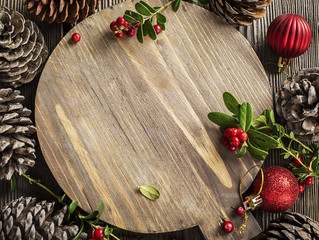Top view winter New Year's Christmas from a round wooden board surrounded by large pine cones, cranberry berries, red Christmas tree balls on a wooden rustic background. Top View.