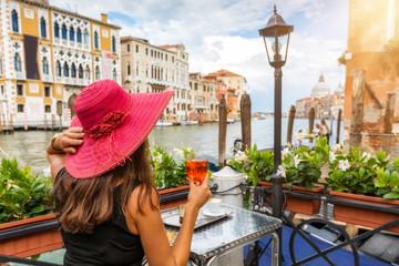 Touristin sitzt am Canale Grande in Venedig, Italien, und genießt einen Aperitif