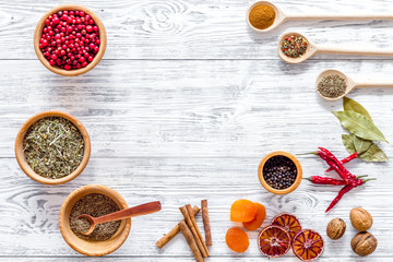 Colorful dry herbs and spices for cooking food light wooden kitchen table background top view space for text