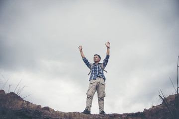 Hiker cheering elated and blissful with arms raised in the sky after hiking.