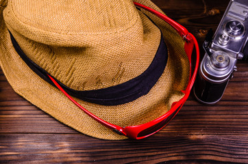 Old rangefinder camera, sunglasses and hat on a wooden table