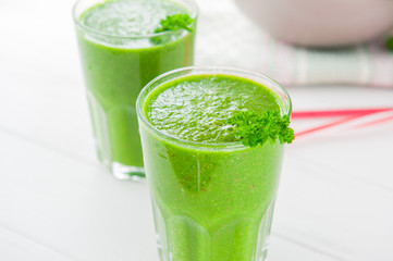 Fresh green Spinach smoothies in glass on the white wooden background. Healthy lifestyle concept. Selective focus. Backlight. Copy space.