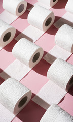 Toilet paper rolls on pink background.