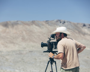 Filmmaker using digital cinema camera, composing shot, desert in distance