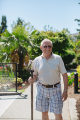 Happy, older caucasian man gardening on sunny day - looking at camera