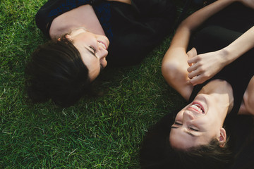 Friends lying in the grass and laughing