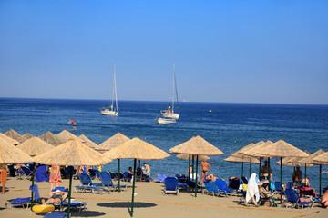Parasole i leżaki na plaży wzdłuż morza.