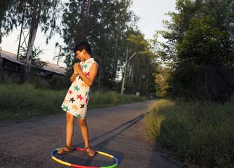 Teenage girl making fun with Hula hoop