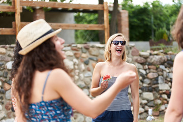Laughing blonde in sunglasses with piece of watermelon