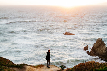 lifestyle image of young female woman exploring windy coast pacific ocean
