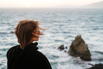 young woman with hair blowing at coast during sunset