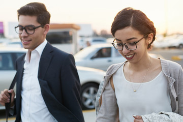 Young startup partners chatting while walking at parking garage