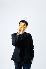 Portrait of an asian man holding a yellow glass in front his face.