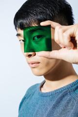Portrait of an asian man holding a green glass.