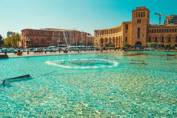 Fountains and architectural complex on Republic Square. Touristic architecture landmark. Sightseeing in Yerevan. City tour. Government House. Travel and tourism concept. Sunny autumn day. Copy space
