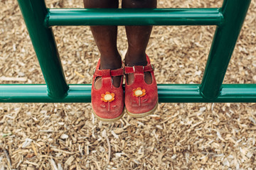 Black girl's feet climbing at a park