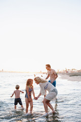 Family on beach at golden hour playing in water