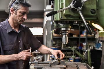 Mature craftsman drilling component in workshop