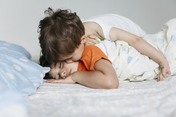 1 year old boy kissing his brother