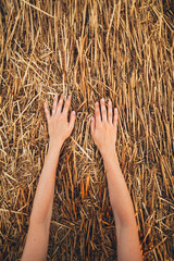 part of hands on sloping field