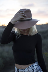 Woman holding her hat during sunset
