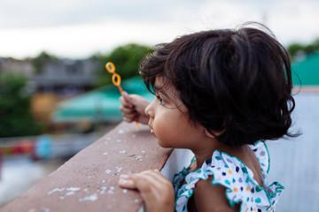 Little girl peeking over a wall