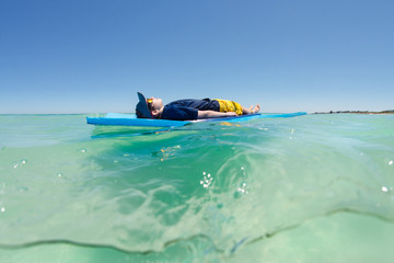 Over under image of a boy floating and relaxing on a large foam mat at the beach in summer