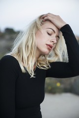 Blonde woman holding hair with eyes closed
