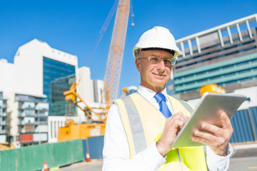 Construction manager controlling building site and tablet device in his hands