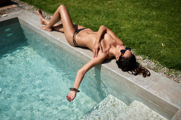 summer time (unfocused) Sexy topless young brunette sunbathing near pool