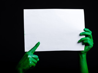 Green zombie hands holding a white sheet of paper. Halloween Theme