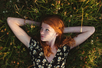 A teenage girl laying in a field in the summertime