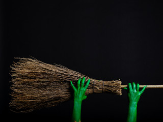 Green zombie hands with a broom. Halloween Theme