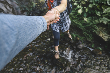Close-up Of Helping Hand, Hiking Help Each Other. Focus On Hands. People Teamwork Hiking With Motivation And Inspiration. Wide angle lens