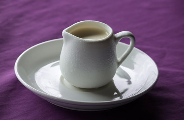 White ceramic creamer on a saucer with cold cream on a purple background.