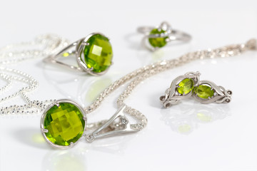 Close-up beauty silver earrings and pendant with peridot on background  chain and rings on white acrylic desk.