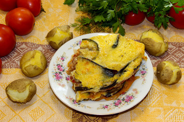 Hot ready moussaka is served on a porcelain plate among vegetables and spicy herbs. Fresh vegetables for cooking light dinner, Moussaka - a traditional Greek dish step by step cooking process