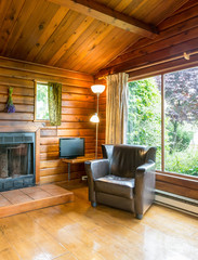 Cozy interior of a rustic log cabin with a garden view.