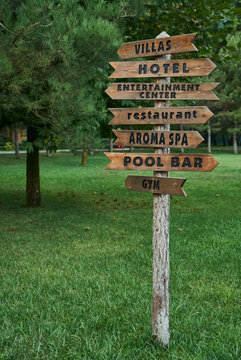 Wooden street signs in the recreation center. Blank street sign post. Crossroad signpost with directions to villas, hotel, entertainment center, restaurant, aroma spa, pool bar and gym