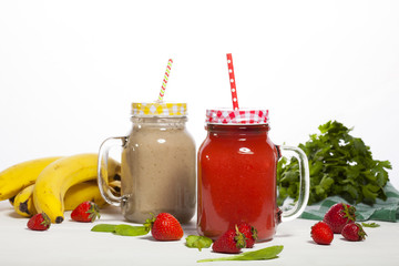 Assortment of fruit and vegetable smoothies in glass bottles with straws