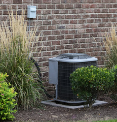 Air Conditioner Near House Surrounded By Shrubs