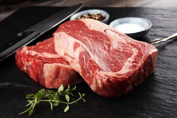 Door stickers Meat Raw fresh meat Ribeye Steak, seasoning and meat fork on dark background