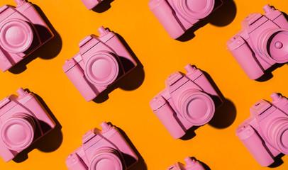 Pink cameras arranged on orange/yellow background.