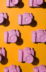 Pink cameras arranged on orange/yellow background.