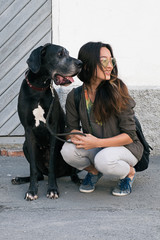 Portrait of asian girl with black dog looking down the street