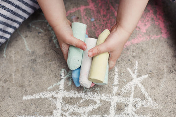 Child drawing with chalk on the floor